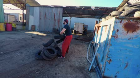 Athlete is training by throw old tire in a junkyard (slow motion) FDV