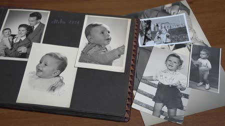 sepya : a man is leafing at vintage photo album to look for old memory and nostalgia of lost childhood FDV Stok Video