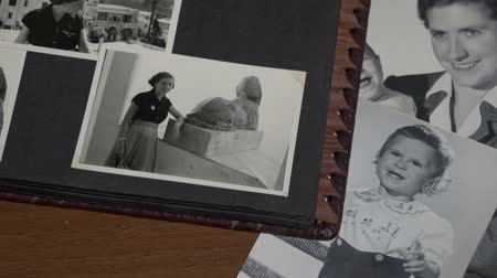 sepya : Foreground slow motion of Browsing a vintage photo album with family in Italy FDV