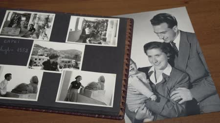 sepya : Browsing vintage album with a lot of photos of mother, father and son. FDV
