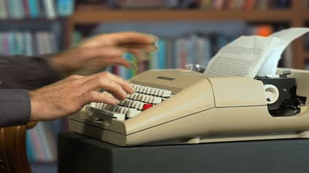 máquina de escrever : Hands of man typing on a vintage typewriter writing a novel MF