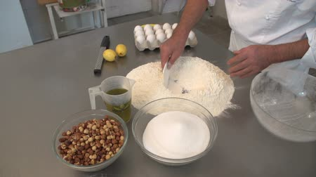 An italian pastry chef is Preparing cakes and pastries mixing eggs. 16 SF
