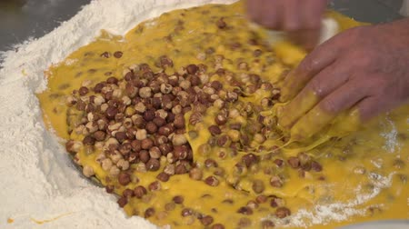 An italian pastry chef is mixing eggs, flour, hazelnuts and sugar making traditional cookies 21 SF