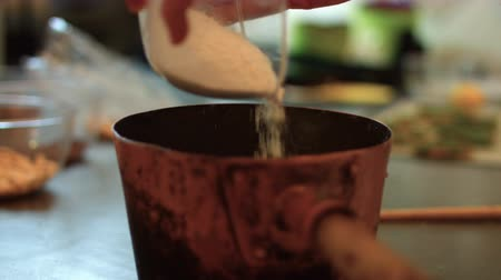An italian pastry chef is Pouring crushed nuts in a copper pot with honey k13 SF