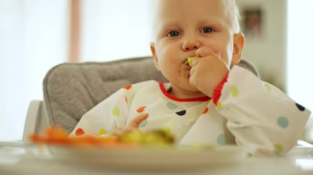 infante : Baby boy eating carrot and broccoli with BLW method, baby led weaning. Happy vegetarian kid eating lunch. Toddler eat himself, self-feeding.