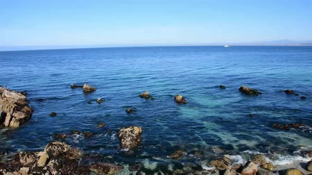 Calm waters in Monterey Bay as water laps at the rocks on the beach. Camera panning right to left. Stock Footage