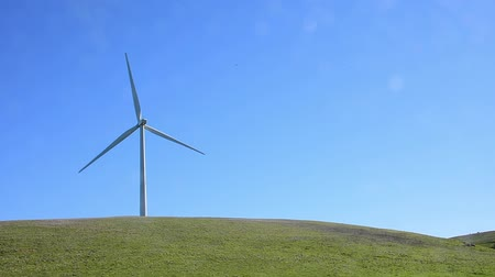 Windmill in a green hilly pasture. Windmill left one third. Camera locked.