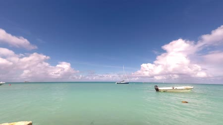 Timelapse of Caribbean scene with boats anchored and bobbing in the breeze. Camera panning left to right. Stock Footage