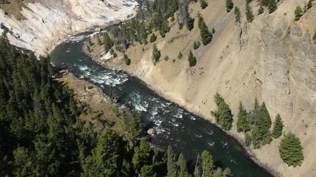 Yellowstone River at Calcite Springs. Camera tilts up revealing Calcite Springs to the left of the river. Camera handheld. Stock Footage