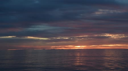 Sunset on the ocean with nearly overcast clouds, lighted from underneath. Camera fixed.