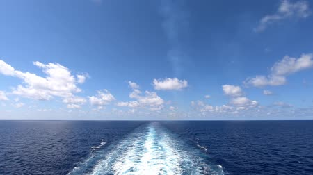 View from the back of a ship traveling at sea. Wake of ship is visible with clouds passing overhead. Camera fixed.