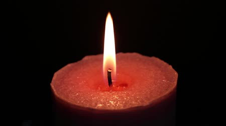 wosk : Close up of a pink candle burning against a black background.