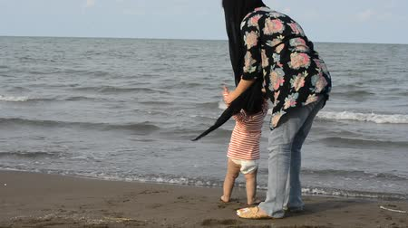 pelenka : Mother and young child with diaper walking at beach, one years old first experience in toddling, parenting and teaching concept