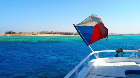 Czech flag on the boat. Adventure tourist vacation ship in the blue sea with flag. Flag on ship, blue sea background, empty desert coastline. Стоковые видеозаписи
