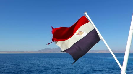 Egyptian flag in the wind above the Red sea. Flagpole on ship with moving banner. Red sea adventure ship with Egyptian flag.