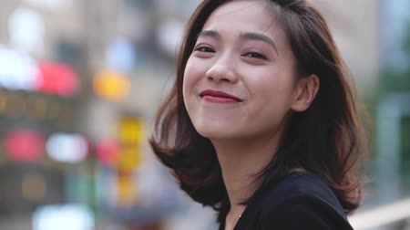 head portrait : Close up of one Chinese girl turn back looking at camera smile in slow motion at city street. Stock Footage