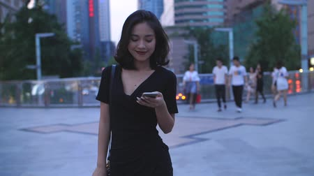 on the phone : One pretty young asian girl walking in the city street with mobile phone in hand, in slow motion