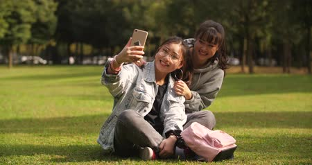 chatování : Slow motion of two asian teen girl sitting on the lawn using mobile phone taking selfie , video chatting outdoor in the park
