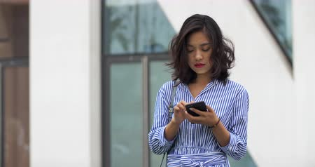 pasu nahoru : One young asian woman using phone in the city with blank face,4k