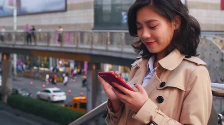 night life : slow motion  of pretty happy young asian woman using mobile phone in the city at afternoon Stock Footage