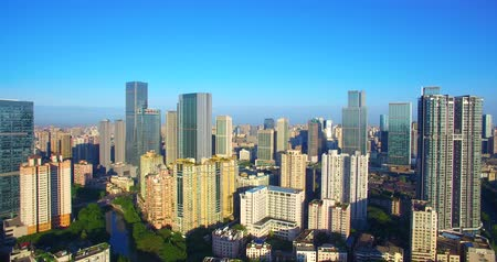 плотный : Aerial camera rise up view of Chengdu City in the morning sunlight, dense residential building near the office building under the blue sky, Downtown Chunxi road business quarter, urban 4k drone clip