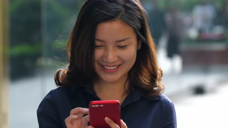 One Young Happy Asian Businesswoman Using Smartphone in the Street with People Walking in the Background at afternoon in slow motion Stock Footage