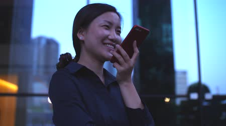 One Young Happy Asian Businesswoman Talking on the Phone by the Office Building Window at evening in slow motion
