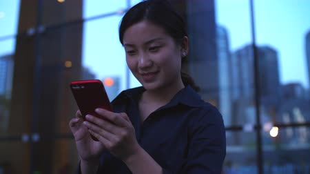 One Young Happy Asian Businesswoman Looking at her Smartphone by the Office Building Window at evening in slow motion Stock Footage