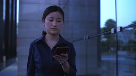 One Young Chinese Businesswoman Looking at Mobile phone Walking by the Office Building Window at evening in slow motion