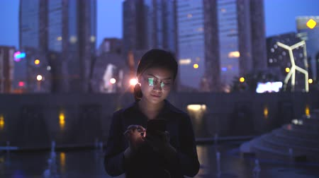 One young Chinese woman touching mobile phone screen at evening with urban night background