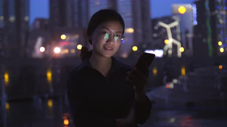 One young Chinese woman looking at mobile phone screen then smile at camera by the fountain at evening with urban night background