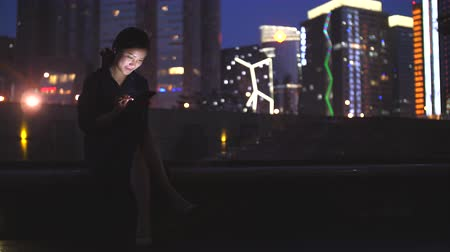 invio : Full length view of One young Chinese woman touching mobile phone screen at evening with urban night background