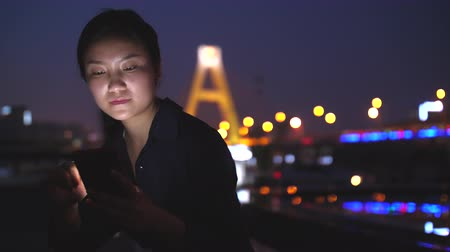 Low angle view of One young Chinese woman touching mobile phone screen and thinking at evening with urban night background