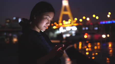 One young Chinese woman touching mobile phone screen and thinking at evening with urban night background Stock Footage
