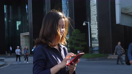 One Young Chinese Businesswoman Looking at Mobile phone Walking by the Office Building with People in the Background at afternoon in slow motion