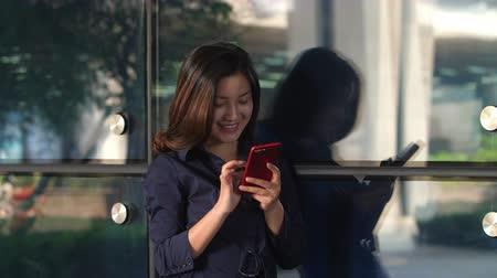 One Young Happy Chinese Businesswoman Using Smartphone by the Office Building Window at afternoon