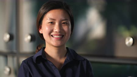 Close up of One Young Chinese Businesswoman Smile at Camera in Slow Motion