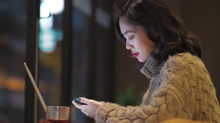Side view of pretty happy Asian woman looking at mobile phone in hand at home. beautiful Chinese girl using smartphone indoor lifestyle 4k clip