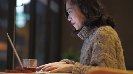 Side view of one pretty young Asian woman busy typing on laptop chatting online in the cafe by the window, Happy Chinese female freelancer busy working on computer,  urban lifestyle 4k clip Stock Footage