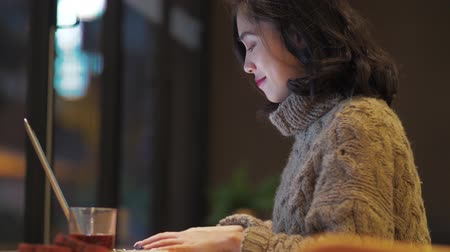 Side view of one pretty young Asian woman busy typing on laptop in the cafe by the window, Chinese female freelancer busy working on computer, working woman urban lifestyle 4k clip.