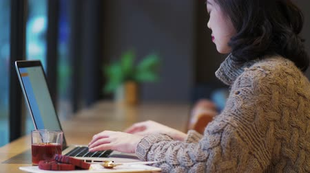 Side view of one pretty young Asian woman typing on laptop in the cafe by the window, female freelancer busy working on computer, looking at the mobile phone and keep typing.urban lifestyle 4k clip.