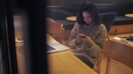 Through the window view of one lovely happy Chinese girl using a mobile phone in cafe with laptop on the table. female freelancer working at night, urban lifestyle with mobile technology 4k clip