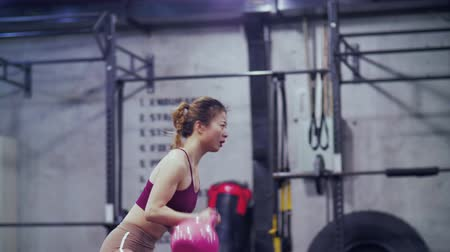 Side view of one Athletic Beautiful young Asian girl working out in the gym, Young pretty sporty Chinese woman exercising in the fitness club using kettlebell. female bodybuilding 4k clip Stock Footage