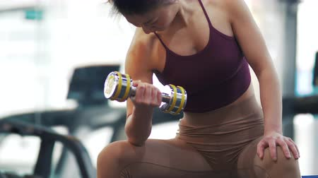 fisiculturismo : Close up of one fitness young Asian woman working out with dumbells at gym. Female Chinese girl with muscular body exercise with dumbells at fitness club. Young Asian female healthy lifestyle 4k clip