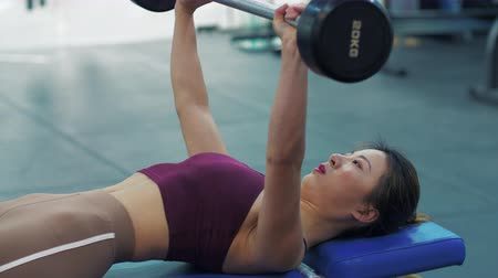 Close up of one fitness young Asian woman working out with barbells at gym. Female Chinese girl with muscular body exercise with barbells at fitness club. Young Asian female healthy lifestyle 4k clip Stock Footage