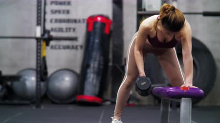 немой : Front view of one Athletic Beautiful young Asian girl working out in the gym, Young pretty sporty Chinese woman exercising in the fitness club using dumbells for muscles. female bodybuilding 4k clip