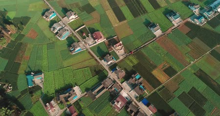 Aerial above view of village house and farm land in morning sunlight at Sichuan China, two cars driving on the road. Beautiful Chinese New Countryside 4k landscape footage.