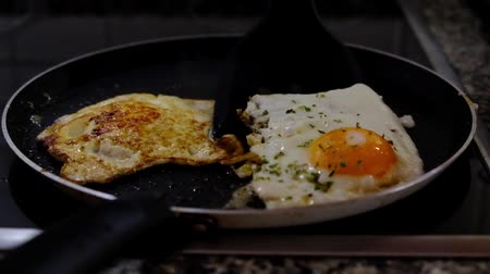 Two eggs being fried on the frying pan Стоковые видеозаписи