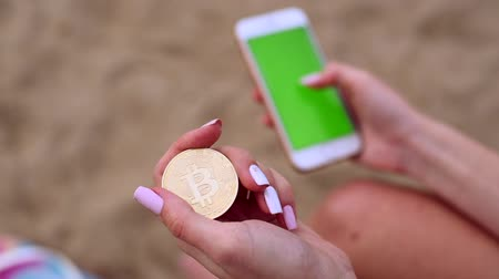 Female hands with bitcoin and mobile phone