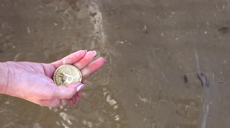 Female hands getting gold bitcoin out of the water Стоковые видеозаписи